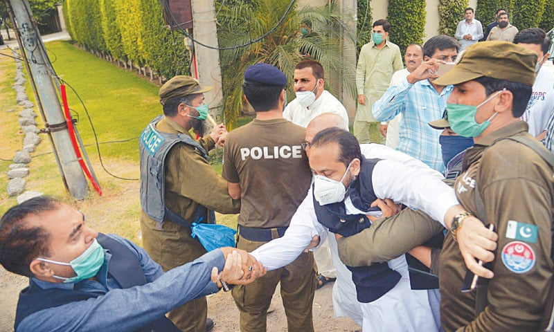 LAHORE: Activists and supporters of the Pakistan Muslim League-Nawaz scuffle with police outside opposition leader Shahbaz Sharif's Model Town residence on Tuesday.—Online