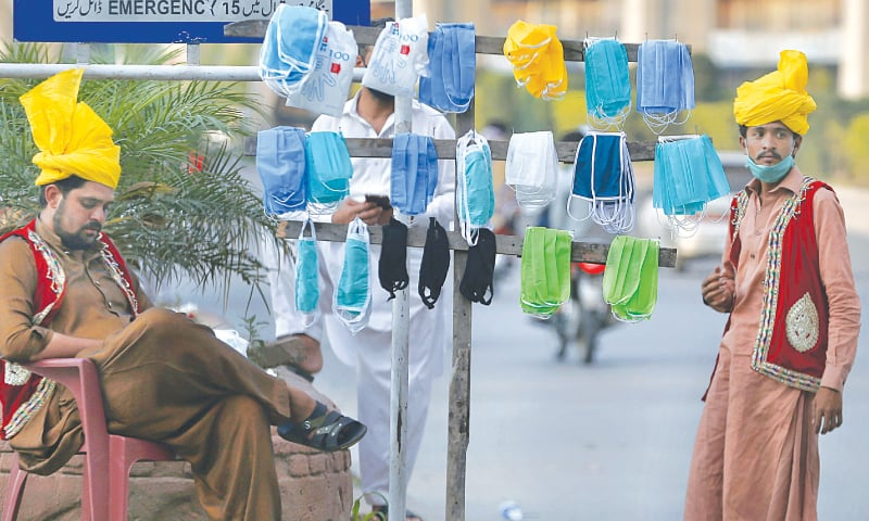 RAWALPINDI: Traditional drummers and dancers selling face masks by the roadside on Tuesday.—AP