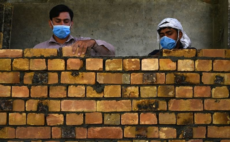 Workers wearing facemasks lay a brick wall at a construction site during a government-imposed nationwide lockdown as a preventive measure against the spread of the COVID-19 coronavirus, in Islamabad on May 6, 2020. (Photo by Aamir QURESHI / AFP) — AFP or licensors