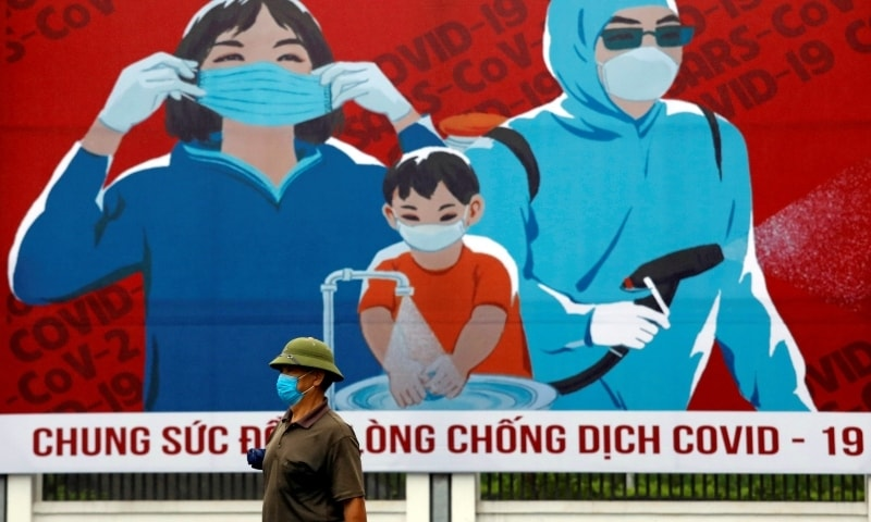 In this file photo, a man wears protective mask as he walks past a banner promoting prevention against the coronavirus disease in Hanoi, Vietnam on April 3.  — Reuters