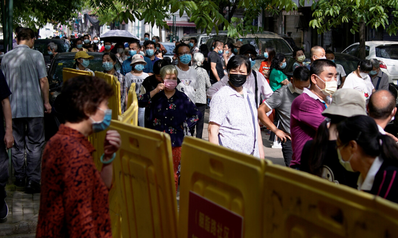 Residents wearing face masks line up for nucleic acid testings at a residential compound in Wuhan, Hubei province, China May 17. — Reuters