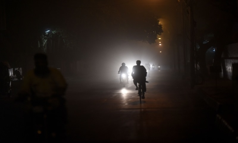 Motorists and cyclists ride on a street in Karachi during a dust storm on June 3. — AFP