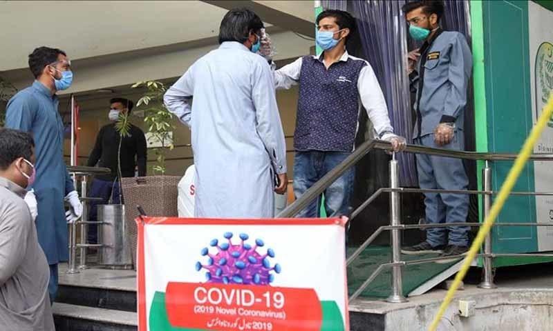 دفتر میں داخل ہونے سے قبل لوگوں کے جسم کا درجہ حرارت چیک کرنے کا ایک منظر — تصویر: ریڈیو پاکستان