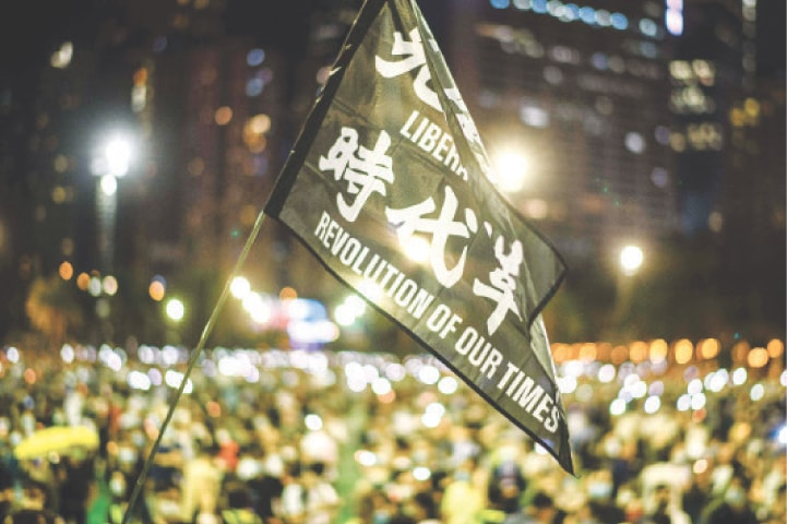 VICTORIA PARK (Hong Kong): Protesters raise a flag that reads 'Liberate Hong Kong Revolution Of Our Times' on Thursday to mark the 1989 Tiananmen Square crackdown.—AFP