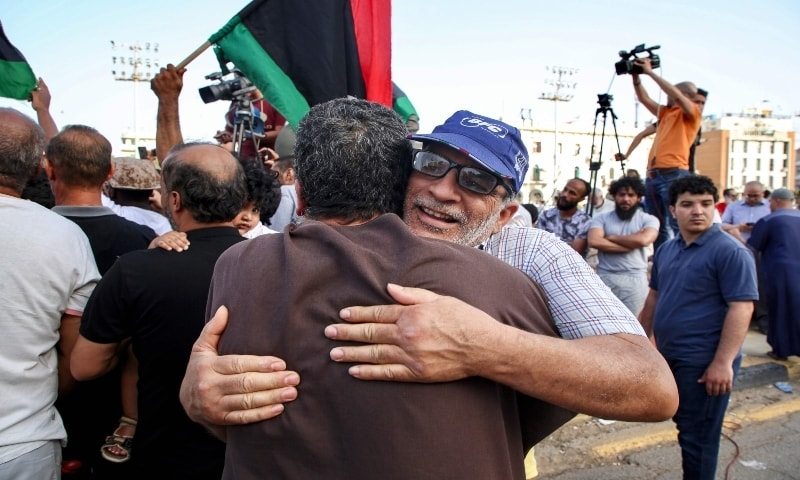 Men embrace as people celebrate in the Libyan capital Tripoli on June 4, 2020, after the UN-recognised Government of National Accord (GNA) said it was back in full control of the capital and its suburbs. — AFP