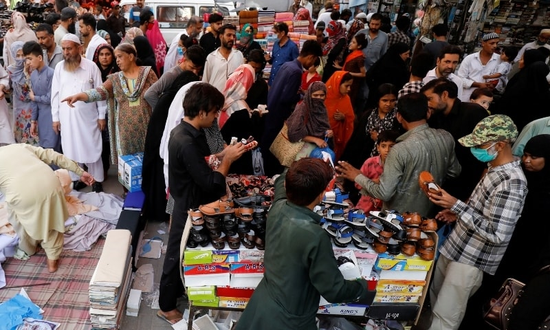 This file photo shows people shopping from stalls ahead of Eidul Fitr in Karachi on May 21. — Reuters