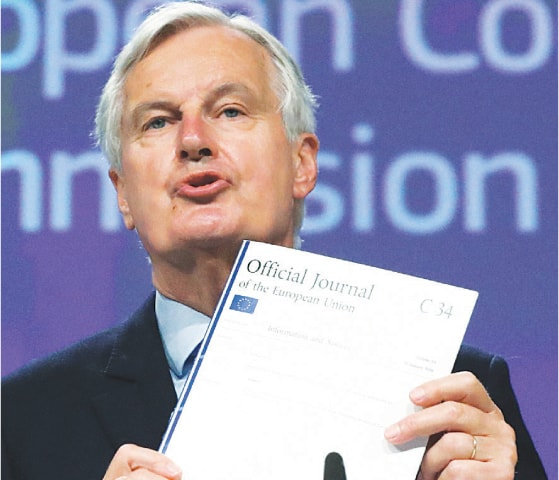 EU's Brexit negotiator Michel Barnier shows documents at a press conference on Friday.—AFP