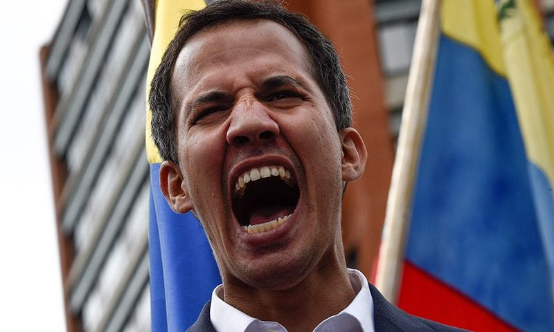 """TOPSHOT - Venezuela's National Assembly head Juan Guaido shouts as he speaks to the crowd during a mass opposition rally against leader Nicolas Maduro in which he declared himself the country's """"acting president"""", on the anniversary of a 1958 uprising that overthrew a military dictatorship, in Caracas on January 23, 2019. - """"I swear to formally assume the national executive powers as acting president of Venezuela to end the usurpation, (install) a transitional government and hold free elections,"""" said Guaido as tho"""