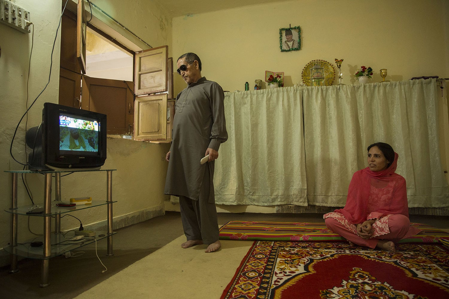 Nusrat Bibi watches television with her father Dost Ali who has been ill for many years, May 18, 2020, in Rawalpindi.