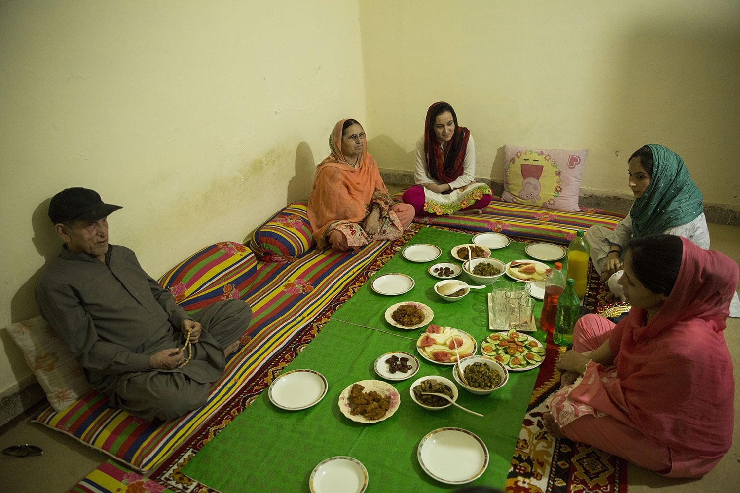 Nusrat Bibi sits down with her family and waits to open her fast during Iftar, May 18, 2020, in Rawalpindi.