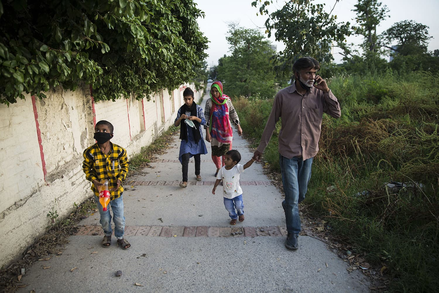 Arif Masih walks his family to the nearby park, an activity they do on a daily basis because they get tired of staying in their one bedroom, April 30, 2020 in Islamabad.