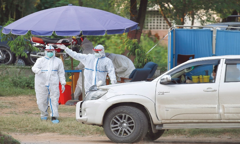ISLAMABAD: Health workers arrive at a drive-through testing and screening facility for the coronavirus on Saturday.—AP