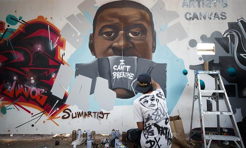 کینیڈا میں ایک فنکار جارج فلائیڈ سے ہکہتی کے لیے ان کی تصویر دیوار پر پینٹ کر رہا ہے— فوٹو: اے ایف پی