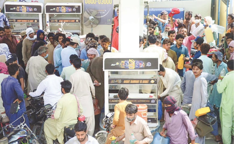 LARKANA: A crowd gathers at a fuel station to get petrol on Monday. Most petrol pumps in Karachi, Hyderabad Lahore, Quetta, and other cities were closed, citing petrol shortage.—PPI