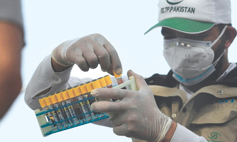 ISLAMABAD: A health official wearing protective gear holds samples taken from people at a drive-through screening and testing facility for Covid-19 on Tuesday.—AFP
