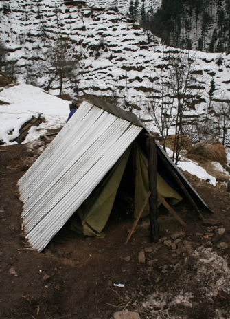 This photo was taken in December 2005 in the Neelum Valley. Shelters after the earthquake reflect differences across households, ranging from a small lean-to to more extensive tents. — Photo by Das
