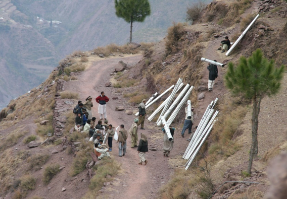 People carrying tin sheets to construct roofs in Neelum Valley in December 2005. Many villages were accessible by jeeps prior to the earthquake, but landslides and other hazards disrupted this transport for up to one year. This particular village was a two hour walk from the road when walking without a load. — Photoby Das