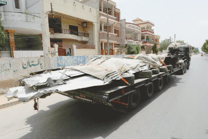 KARACHI: A truck loaded with the wreckage of the crashed PIA plane is pictured after it was retrieved from the roof of a house at the crash site on Wednesday.—Reuters