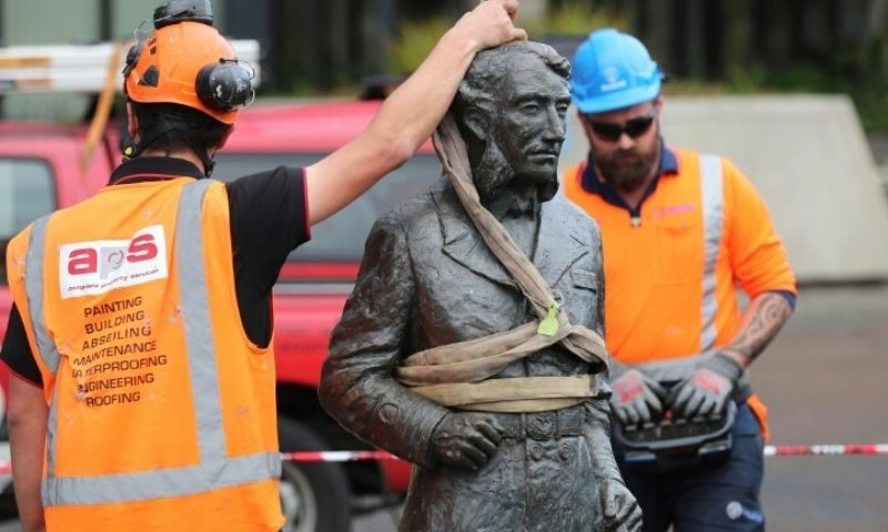 A crane hoists the sculpture of Captain John Fane Charles Hamilton from the city square after requests from Maori and threats from anti-racism protesters to topple it. — AFP