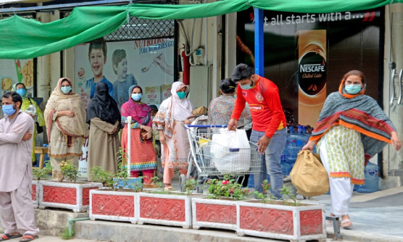 G-9 residents buy essential items on Friday hours before the area was to be sealed following emergence of Covid-19 cases. — Photo by Mohammad Asim