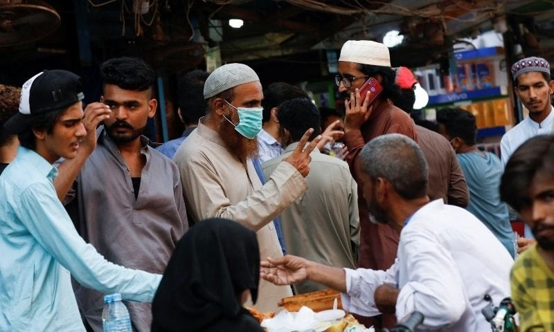 A man wearing a protective face mask gestures while shopping amid the rush of people outside an electronics market in Karachi. — Reuters