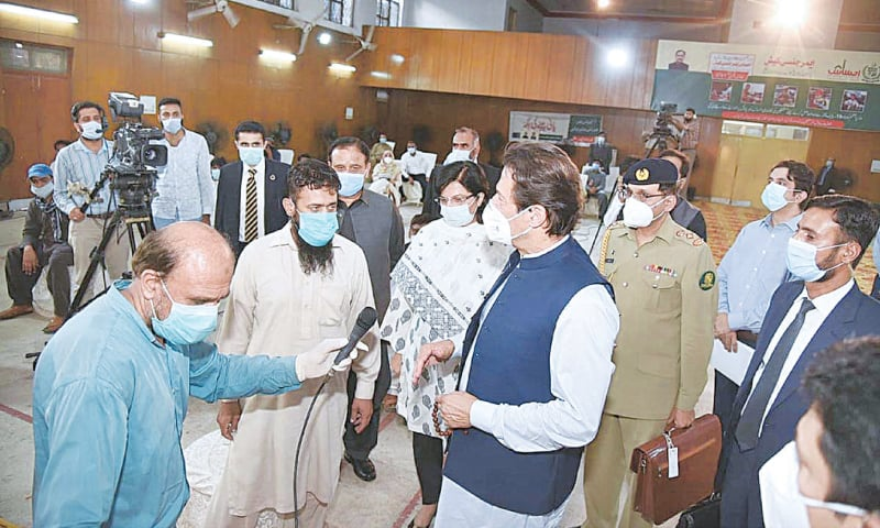 LAHORE: Prime Minister Imran Khan talks to deserving people at an Ehsaas facility.—APP