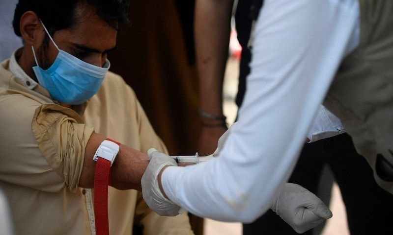 A health official (R) wearing protective gear takes a blood sample from a man at a drive-through screening and testing facility for Covid-19, alongside a street in Islamabad on June 9, 2020. — AFP/File