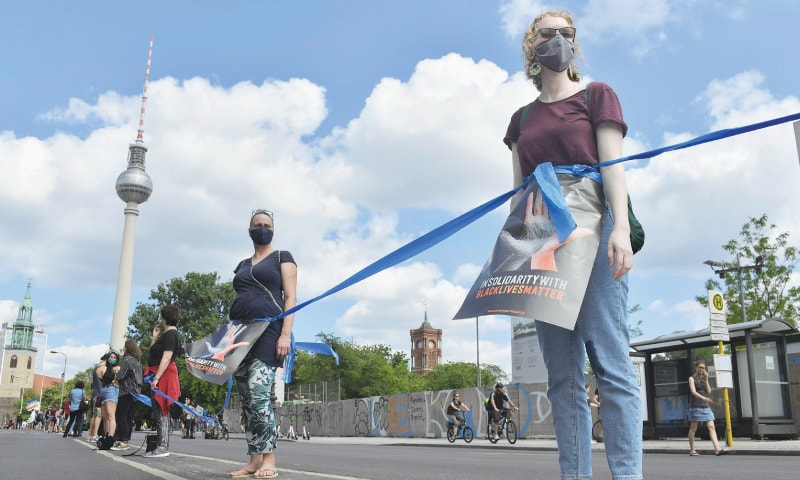 """Berlin: Protesters form a human chain as they take part in a demonstration organised by the """"indivisible movement"""" in front of the Brandenburg Gate on Sunday.—AFP"""
