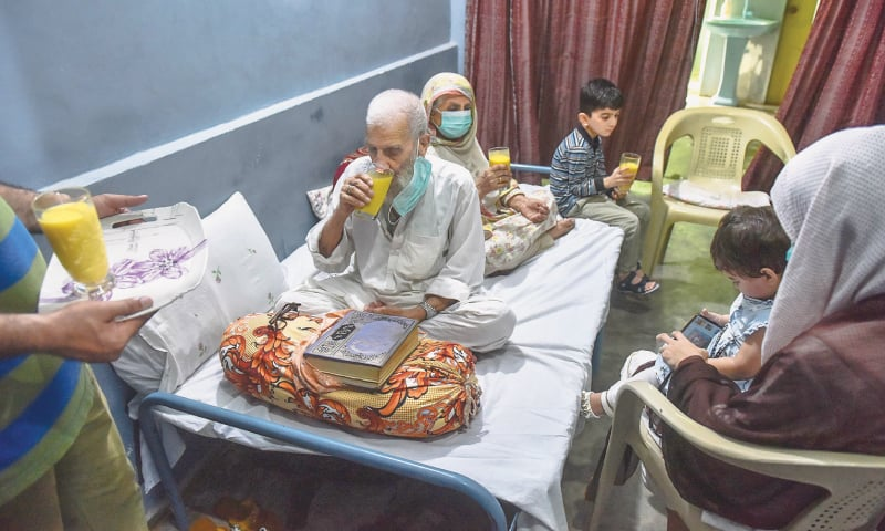 Ninety-year-old Fazalur Rahman with his wife and grandchildren after recovering from the coronavirus. He wants to stay at home for a few more days as a precautionary measure. —Fahim Siddiqi/White Star