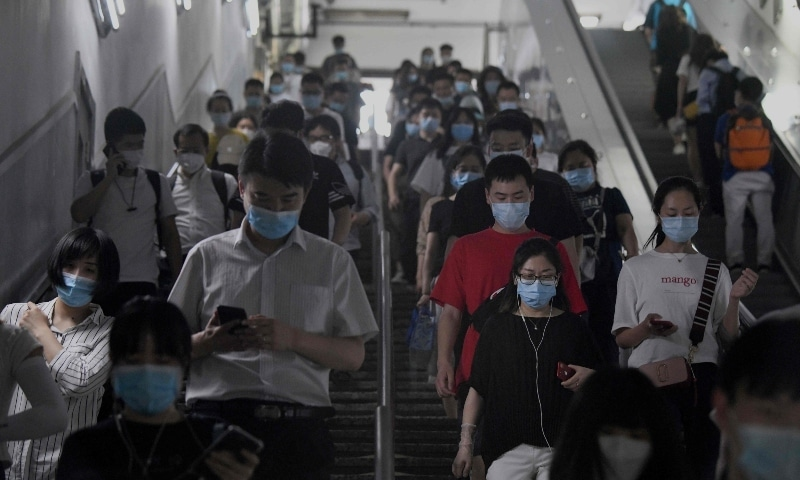 Passengers wearing face masks walk through a subway station in Beijing on June 15. — AFP