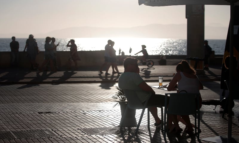 A couple sits in a terrace bar as people walk near the beach of Palma de Mallorca, Spain on Monday, June 15, 2020. — AP