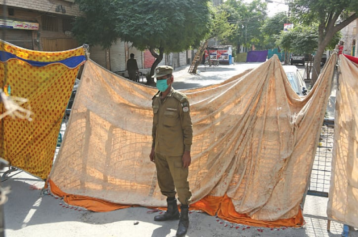 A policeman stands guard outside a street in Islampura that was sealed on Tuesday as part of the government's 14-day smart lockdown. — White Star