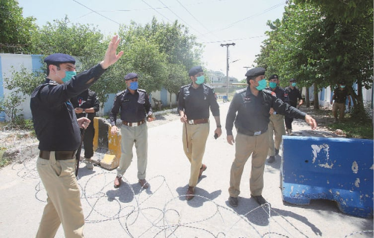 Peshawar: Police officers stand guard at a checkpoint in an area designated as a restricted one to help contain the spread of new coronavirus on Tuesday. Authorities sealed off many areas in different cities following the decision taken on the advice of the Health Department and epidemiologists after hundreds of cases were reported.—AP
