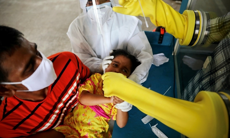 A health worker collects a swab sample from a child at Mugda Medical College and Hospital in Dhaka on June 23. — Reuters