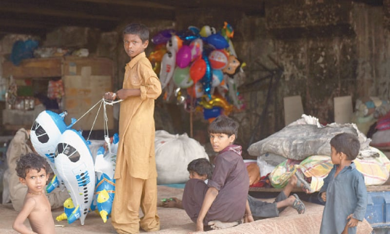 CHILDREN of homeless people pictured with their possessions under a bridge in Nazimabad.—White Star