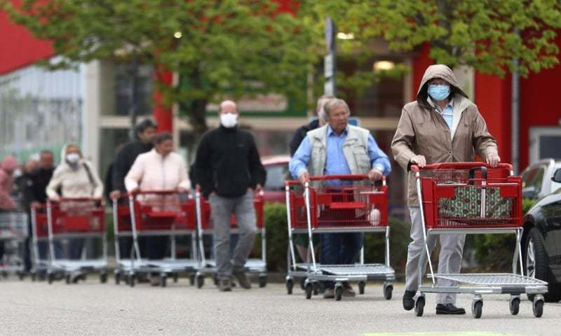 People wearing protective masks queue up to go in a garden store in Munich, Germany in April. — AP