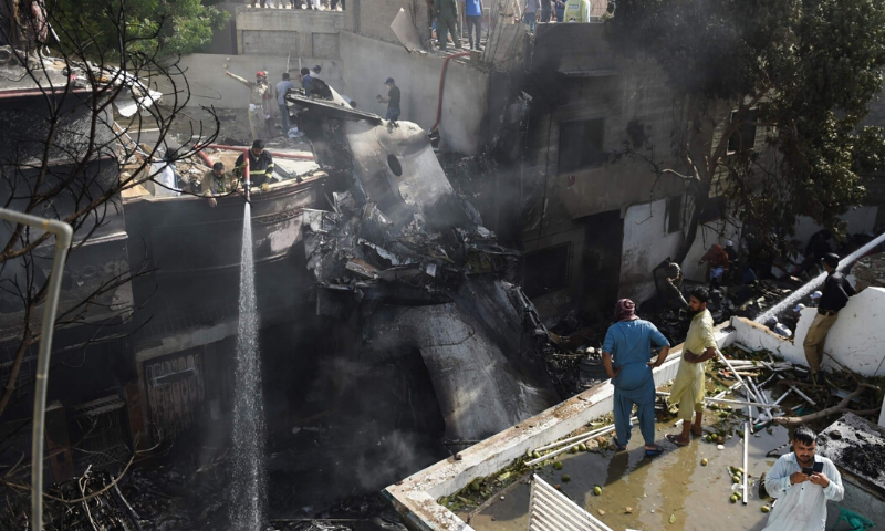 Firefighters spray water on the wreckage of a Pakistan International Airlines aircraft after it crashed at a residential area in Karachi on May 22. — AFP/File