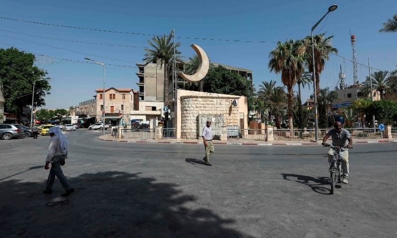 Palestinians pass by on a street of the West Bank city of Jericho on June 21. — AFP