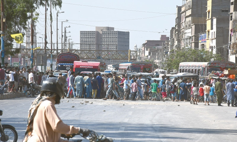 PEOPLE protesting against shortages of water and power supplies in their area block the main road near Teen Hatti bridge on Wednesday. —Faysal Mujeeb / White Star