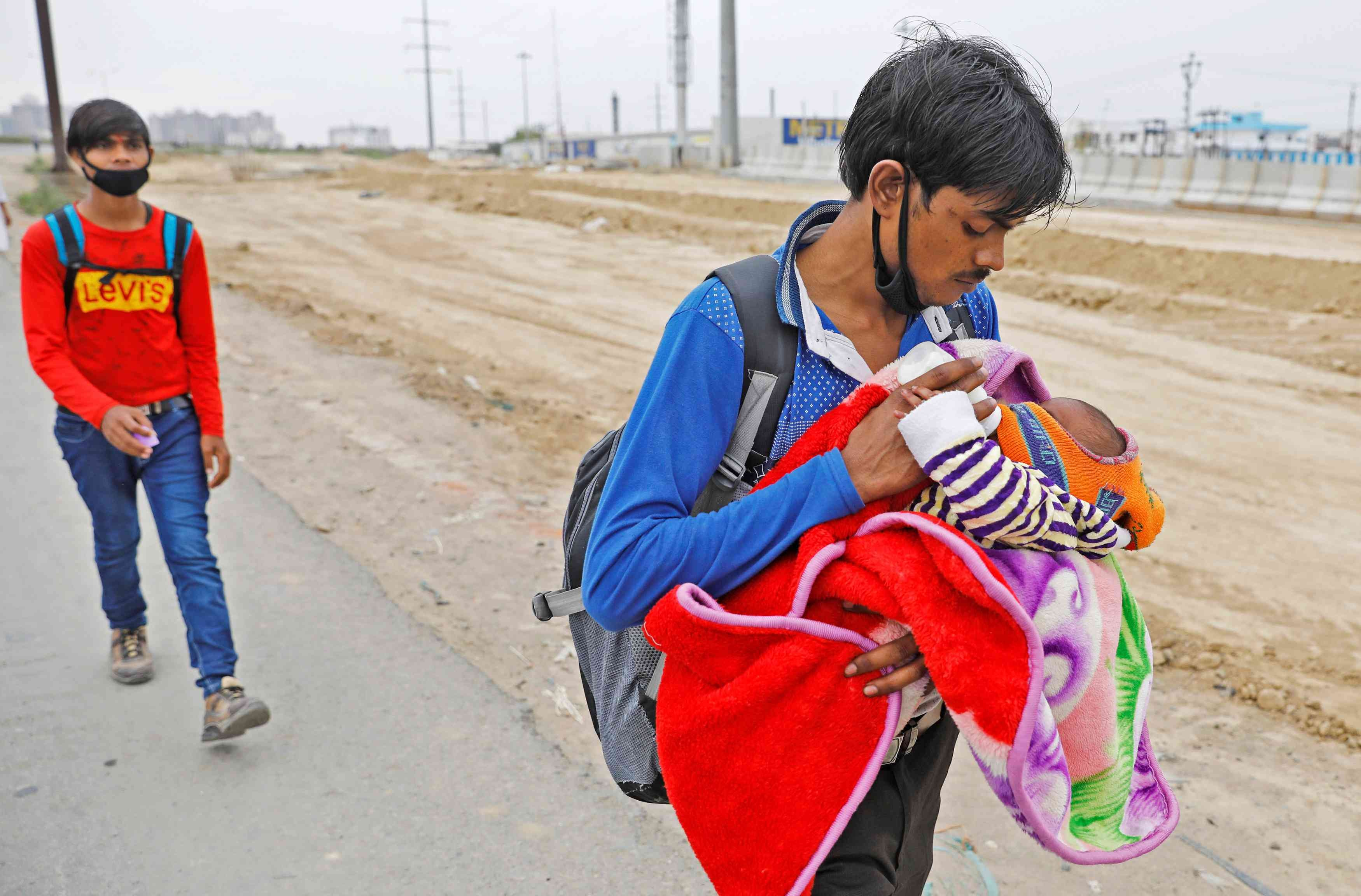 A migrant worker in Ghaziabad feeds his newborn baby as he walks on a highway. — Reuters