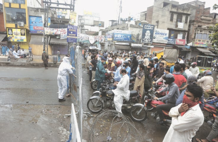LAHORE: A policeman stops motorcyclists from entering an area that has been sealed off with a view to curbing the spread of Covid-19.—AP