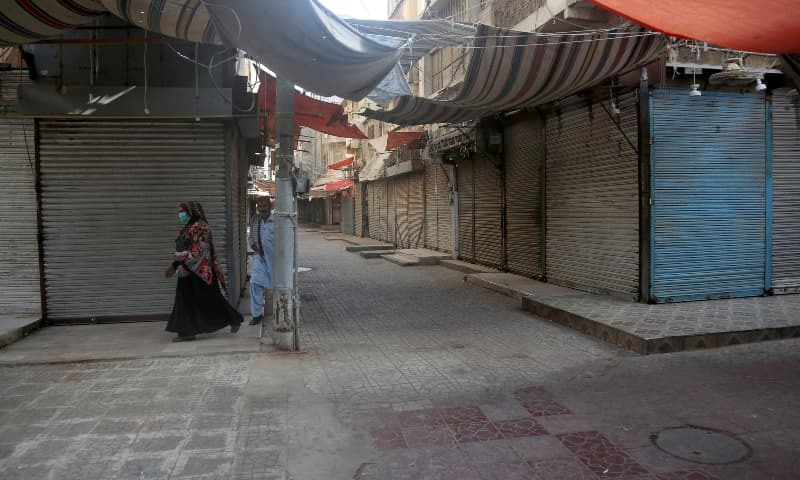 A couple walk in a closed market in a restricted area that is sealed off to control the spread of the new coronavirus, in Karachi. — AP/File