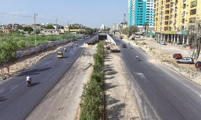 VEHICLES move on main M.A. Jinnah Road on Saturday along the track of the under-construction Green Line bus project. A major portion of the city's main artery had been closed for construction since December 2018. The Sindh governor says buses for the mass transit project are due to arrive in December this year.—Fahim Siddiqi / White Star
