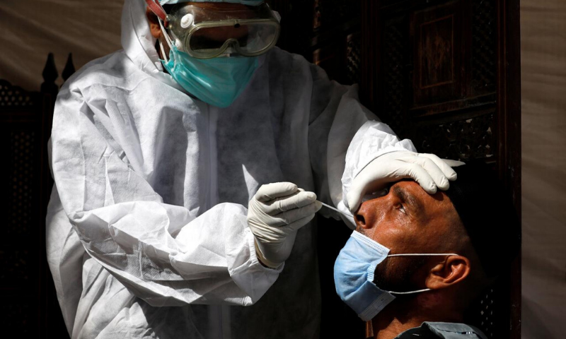 A paramedic wearing protective gear takes a nose-swab sample to be tested for the coronavirus in Karachi. — Reuters