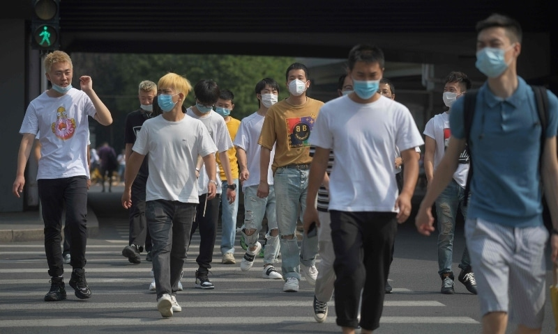 People wear masks as they cross a road in Beijing on June 28. — AFP