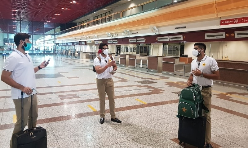 In this handout picture released and taken by the PCB, Babar Azam (R), Imad Wasim (L) and Imamul Haq (C) wearing face masks arrive at Allama Iqbal International airport on June 28. — AFP