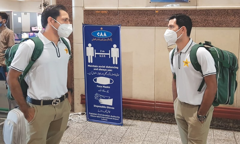 LAHORE: Pakistan cricketers Sarfaraz Ahmed (L) and Asad Shafiq wear facemasks  upon their arrival at the Allama Iqbal International airport ahead of their departure to England on Sunday. — AFP