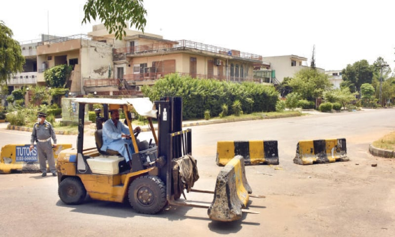 A worker removes a barrier from a road on Sunday after the capital administration decided to open the two sub-sectors in G-9. — Online
