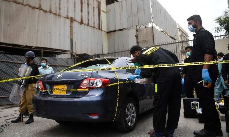 Policemen guard as members of Crime Scene Unit investigate around a car used by alleged gunmen at the main entrance of the Pakistan Stock Exchange building on June 29. — AFP