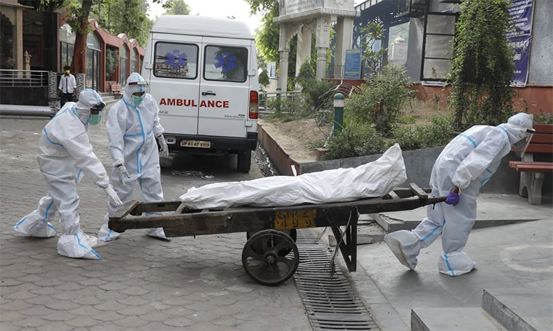 نئی دہلی میں کورونا سے ہلاک ایک شخص کی لاش کو مکمل حفاظتی اقدامات کے ساتھ آخری رسومات کی ادائیگی کے لیے لے جائی جا رہی ہے— فوٹو: اے ایف پی